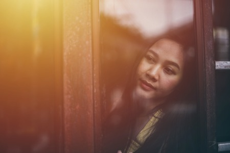 Asian woman standing at the window watching Stock Photo - 122889281
