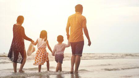 Famiglia asiatica felice che gode della passeggiata sulla spiaggia
