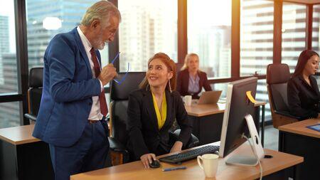 Empleado senior sonriente discutiendo con mujer de negocios en el lugar de trabajo