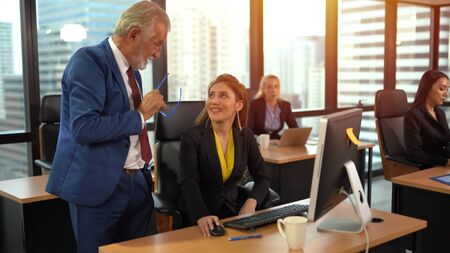 Smiling senior employee discussing with business woman at workplace