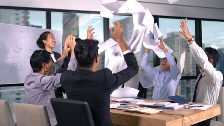 Asian business team throwing paper when meeting success