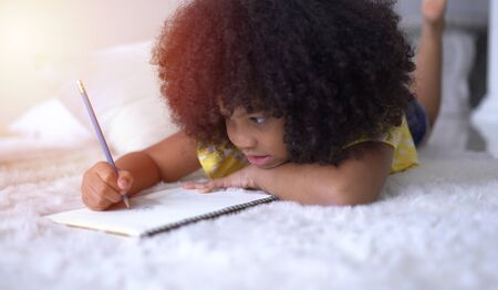 Portrait of cute little African student doing schoolwork
