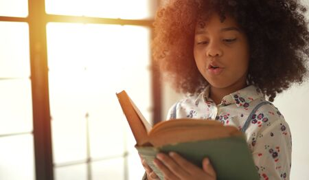 African Girl reading textbook in home 版權商用圖片