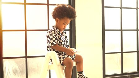 Cute african american boy playing on a mobile phone. 版權商用圖片