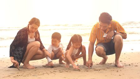 Young family of four sitting and play the sand on the beach