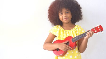 Portrait of happy little smile african girl with guitar