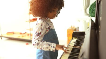 beautiful little african kids are playing on piano music 版權商用圖片 - 135078319