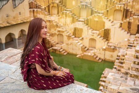 Asian woman posing at Panna Meena Ka Kund stepwell in Jaipur,Rajasthan, India 版權商用圖片 - 136913344