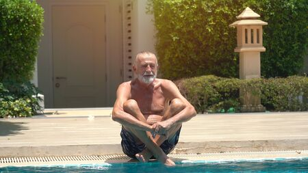 Senior man swimming in an outdoor swimming pool 版權商用圖片 - 136913498