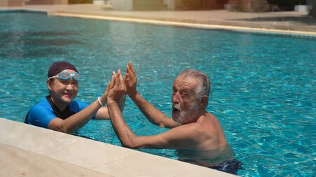 Senior Couple Relaxing In Swimming Pool Together 版權商用圖片 - 136869549