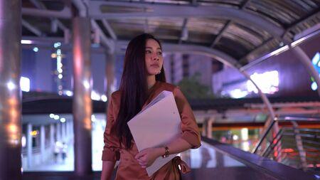 Beautiful young asian woman walking in the night city streets 版權商用圖片 - 136869717