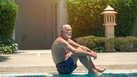 Senior man swimming in an outdoor swimming pool 版權商用圖片 - 136913299