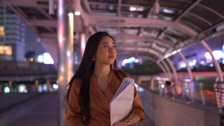 Beautiful young asian woman walking in the night city streets 版權商用圖片 - 136913441