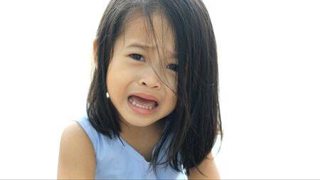 Portrait of crying little asian girl in the house