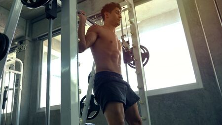 Muscular man working out in gym doing exercises 版權商用圖片
