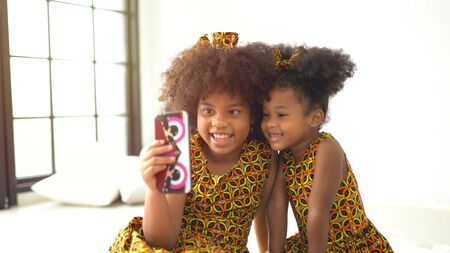 Little cute afro children playing on smartphone