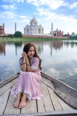 Asian woman posing over Taj Mahal from a boat, Agra, India 新聞圖片