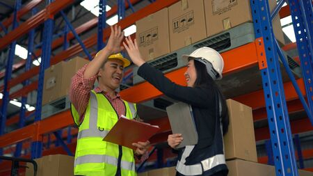 Give me high five. Warehouse worker having fun in the warehouse.