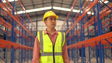 Warehouse worker posting in a large warehouse