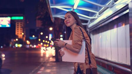 Young asian business woman calling taxi on city street at night