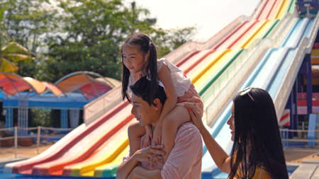 A happy family of mother, father and children, daughter, having fun on vacation at a water park 스톡 콘텐츠