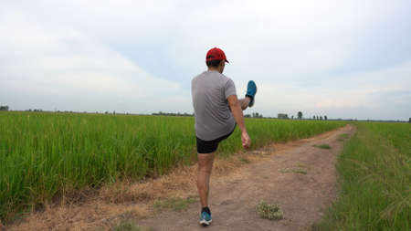 Young man runner jogging exercise healthy lifestyle in green field 版權商用圖片