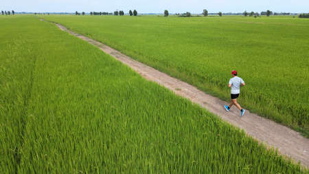 Aerial view of young asian sports man running on green field