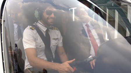 Business man and pilot in small private helicopter on a landing point