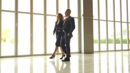 Businessman and businesswoman discussing work while walking in the airport 版權商用圖片