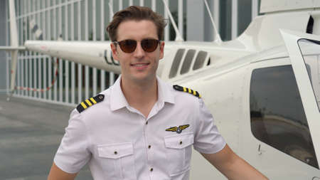 Portrait of commercial pilot in uniform standing near small private helicopter 스톡 콘텐츠