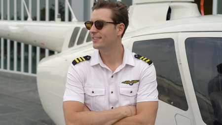 Portrait of commercial pilot in uniform standing near small private helicopter 版權商用圖片
