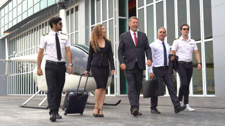 Group of business man and woman walked off a helicopter after returning from traveling at airport