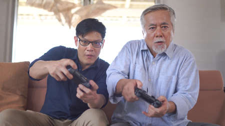 Happy asian father and son enjoy playing video games with joysticks in living room at home 스톡 콘텐츠