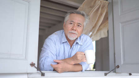 Senior asian man looking by window, holding cup of tea at home 스톡 콘텐츠
