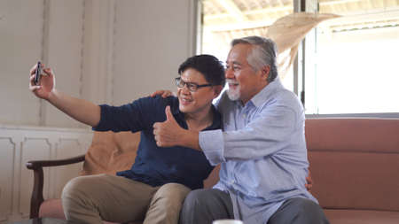 happy asian son taking selfie with retired cheerful father at home