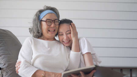Asian senior woman and daughter reading a book at home 스톡 콘텐츠