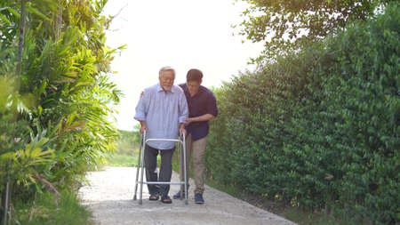 Senior asian man struggling to us a walker. His adult son is helping him