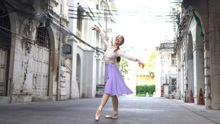 Young beautiful ballerina dancing along the street in Bangkok Thailand