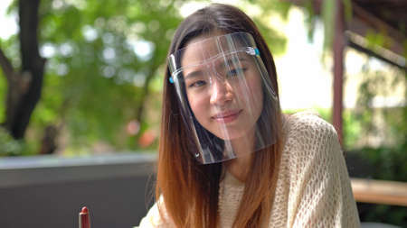 Portrait of young asian woman wearing face mask on green tree