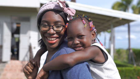African American Mother And Daughter piggyback outdoor at home