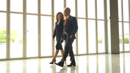 Business man and woman discussing work while walking 스톡 콘텐츠
