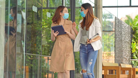 Business asian woman walking together and wear masks to protect and take care of their health