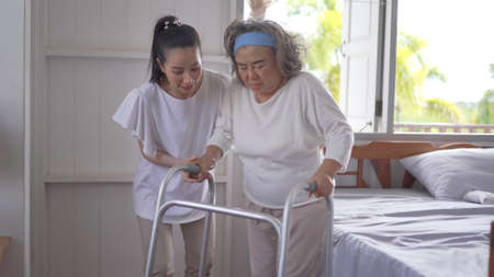 Asian adult woman or daughter support senior mother use walker at home
