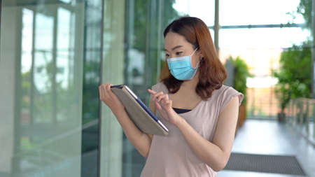 Young asian woman using tablet and wearing face mask on green tree