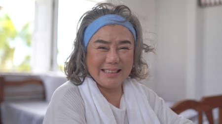 Smiling asian senior elderly woman looking at camera at home