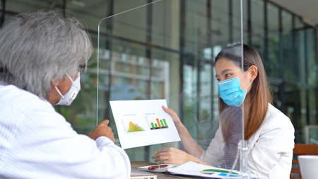 Business asian woman presenting to her boss and wear masks to protect and take care of their health