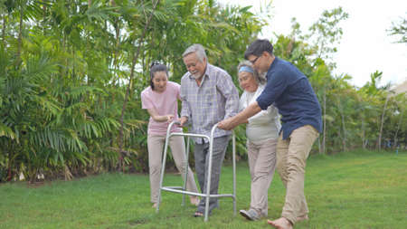 Asian family support senior farther use walker at home 版權商用圖片