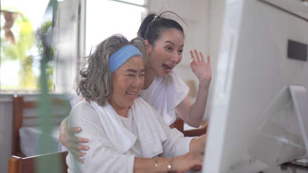 Asian senior woman and daughter video conferencing on computer at home