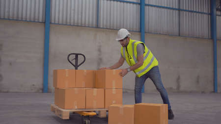 Smiling warehouse workers preparing a shipment in a large warehouse Banque d'images