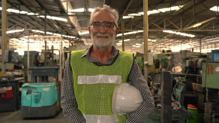 Portrait factory senior man worker on manufacture workshop background Standard-Bild